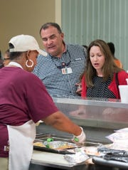 Regulars Benny Gaines and Lindsay Durre make their lunch selections at the All in One Kitchen Ministry at Englewood Baptist Church in Pensacola on Friday, August 10, 2018.