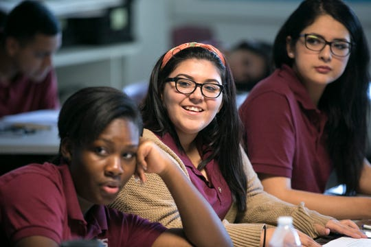 ASU Preparatory Academy seniors Byani Knight (from left), 17, Gabriela Meyer, 18, and Cecelia Moreno, 18, listen during a discussion in English class at ASU Preparatory Academy in Phoenix, May 26, 2015.