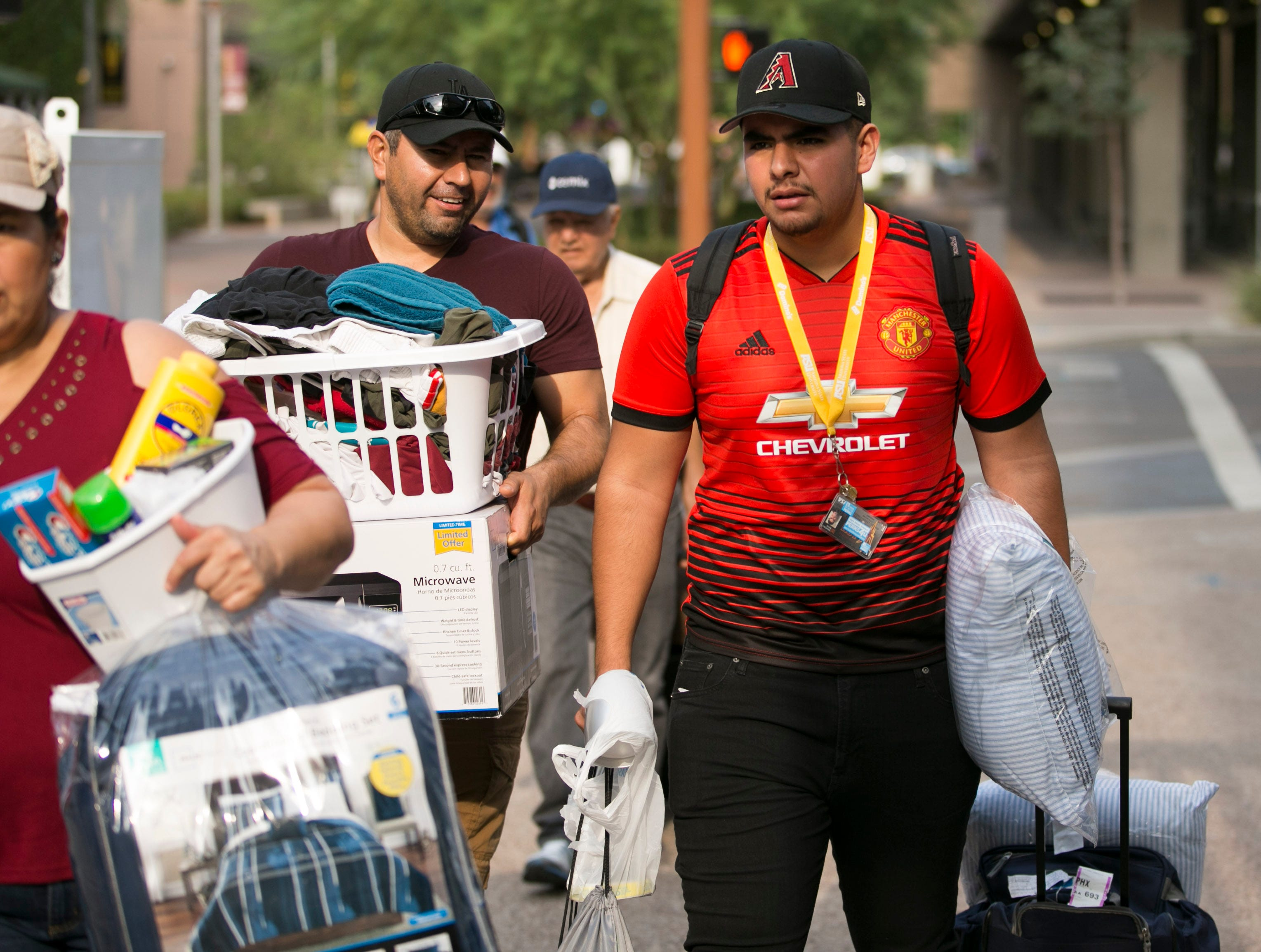 Marcos Leyva (left) of Avondale helps his son, Marcos Jr., an incoming freshman, move into his dorm at Taylor Place on the ASU downtown Phoenix campus on Aug. 10, 2018.