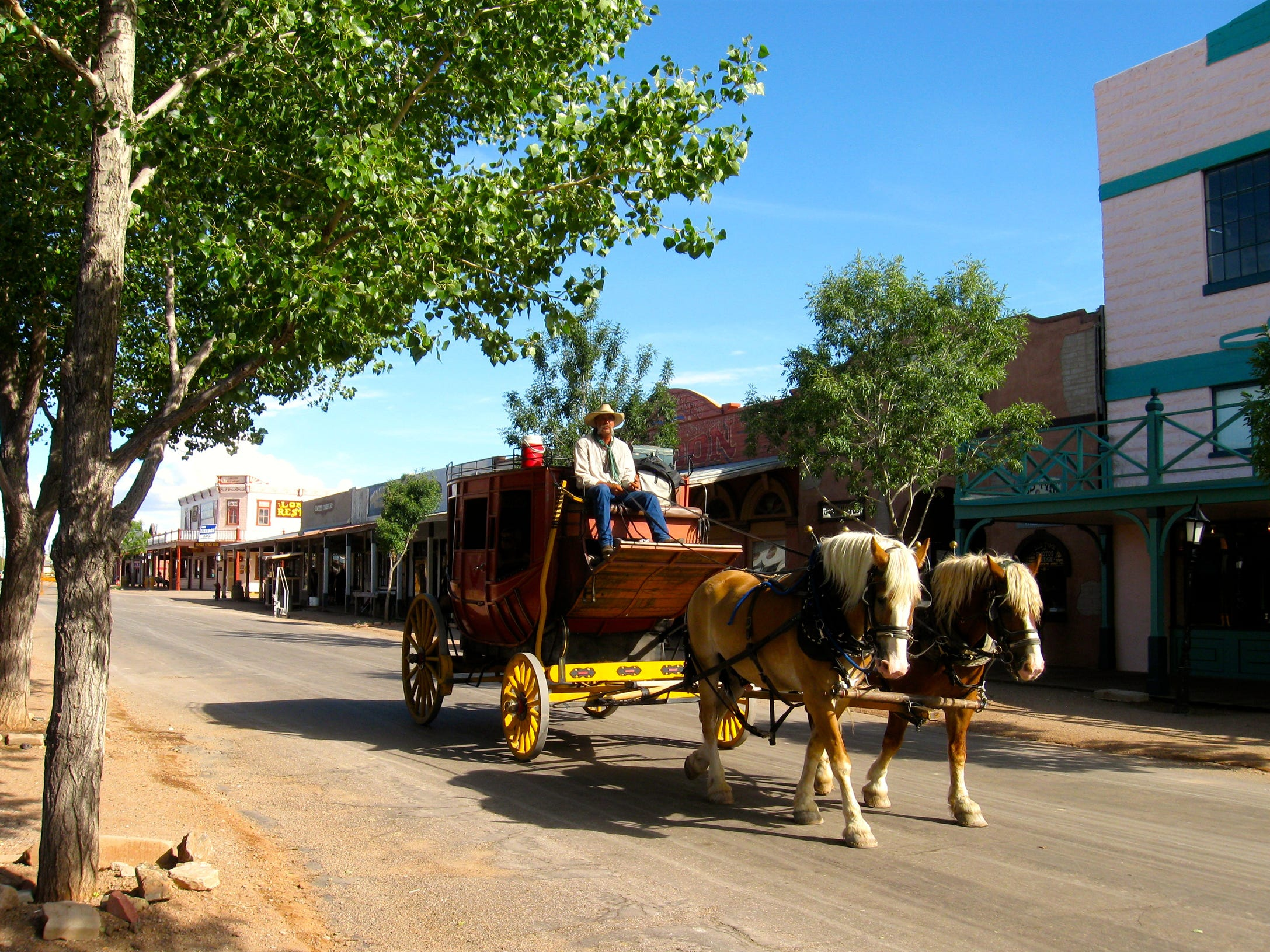 Stagecoaches and covered wagons clop through Tombstone during the daytime. The southern Arizona town depends on visitors wanting to experience the Old West.