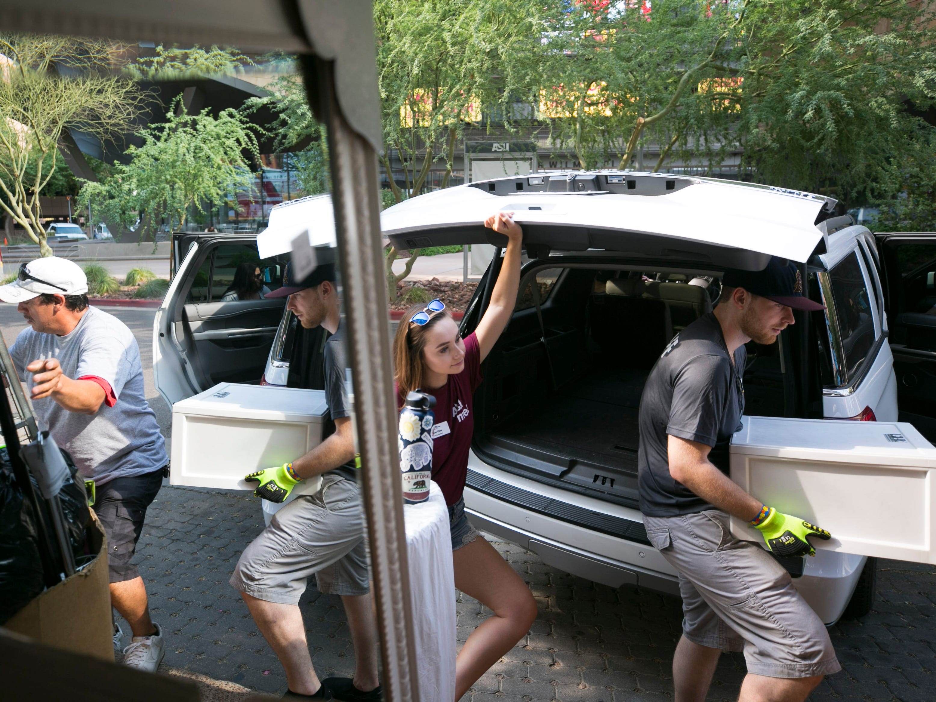 Incoming freshman Claire Stroud (center) of Newbury Park, California, looks on as she receives help moving into her dorm at Taylor Place on the ASU downtown Phoenix campus on Aug. 10, 2018.