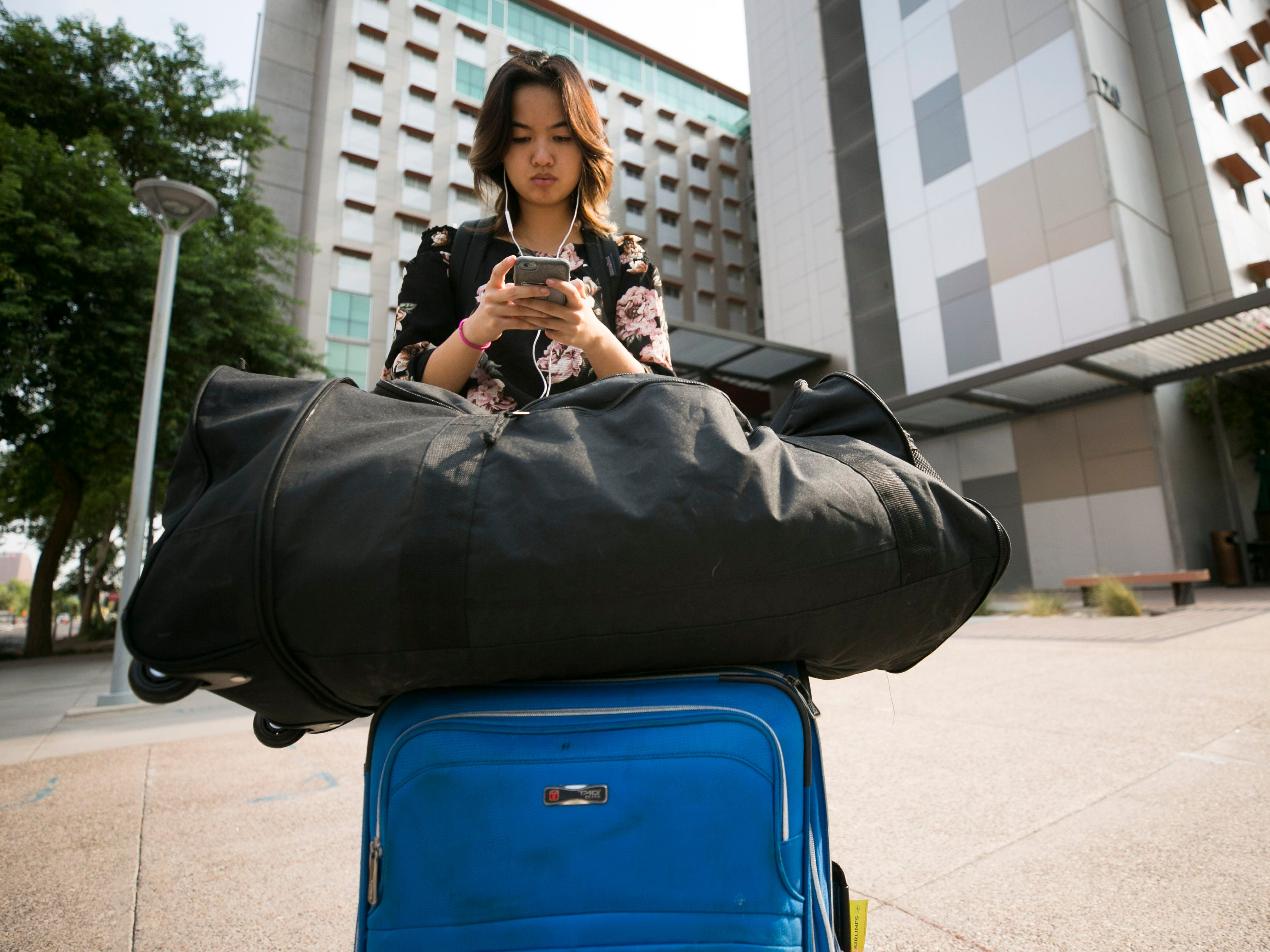 Incoming freshman Lynn Huynh of Casa Grande texts while moving into her dorm at Taylor Place on the ASU downtown Phoenix campus on Aug. 10, 2018.