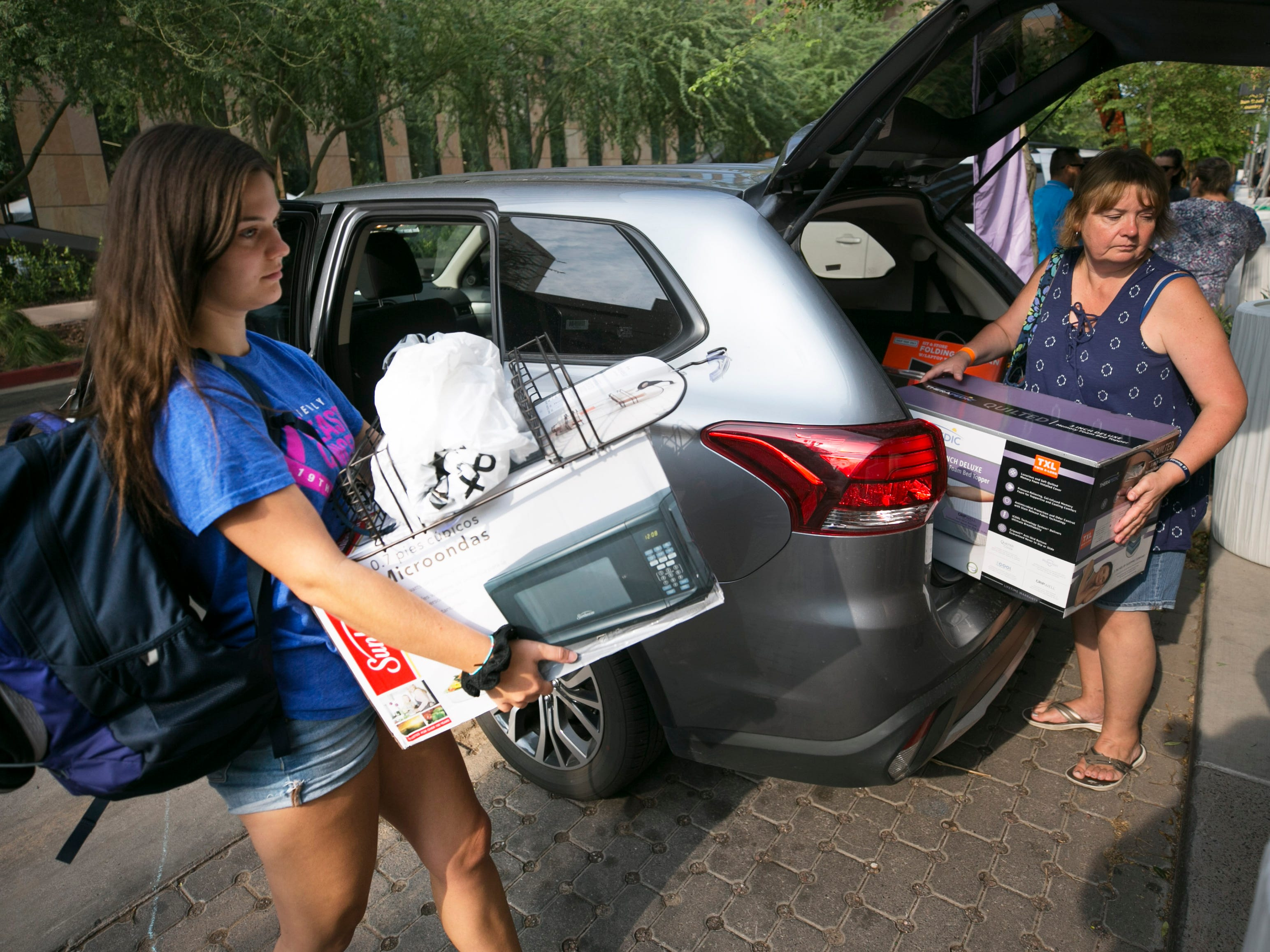 Incoming freshman Bailey Sullivan (left) of Burbank, Illinois, and her mother, Kim Sullivan, move into Bailey's dorm at Taylor Place on the ASU downtown Phoenix campus on Aug. 10, 2018.