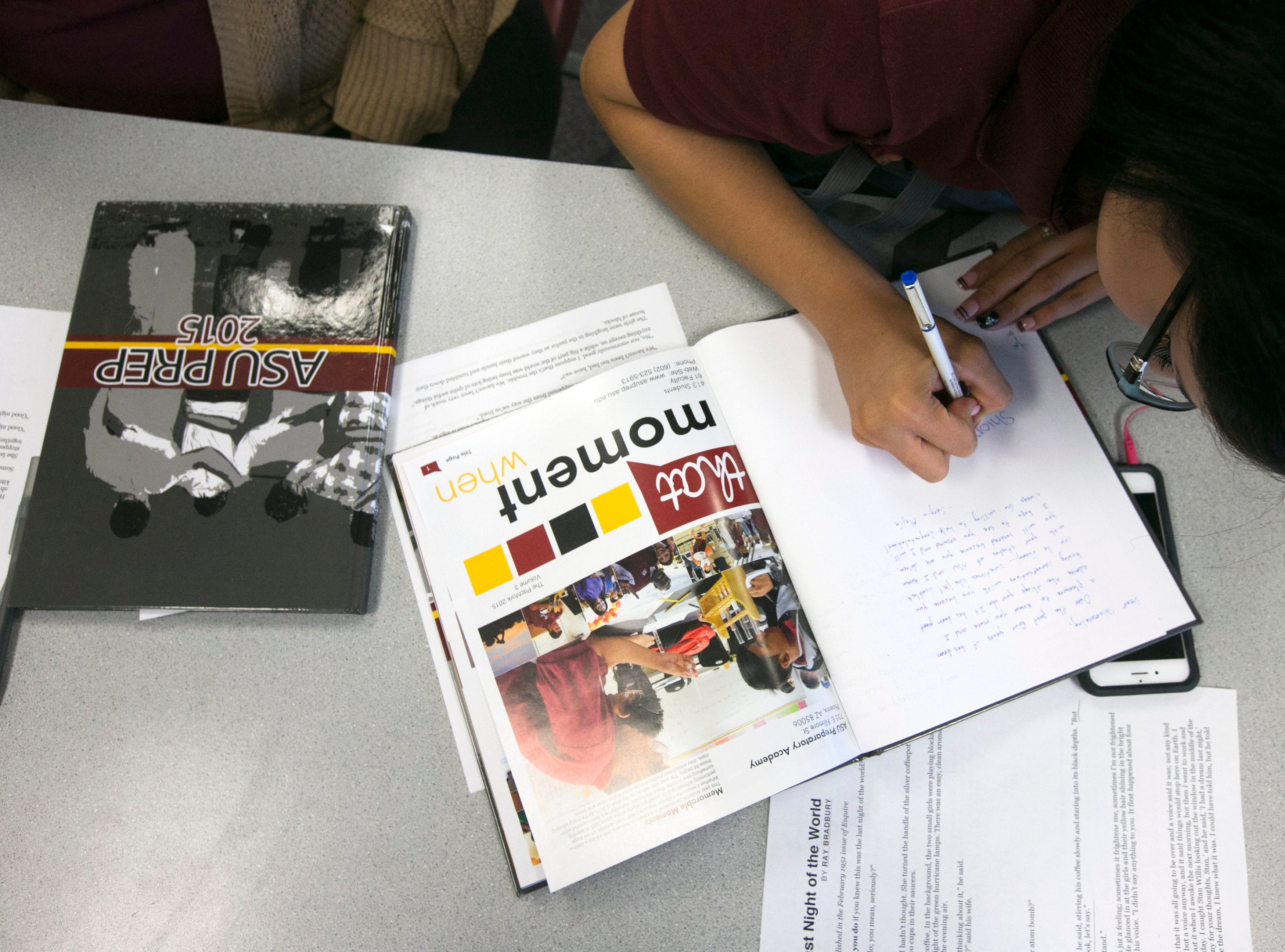 ASU Preparatory Academy senior Cecelia Moreno, 18, signs a yearbook at ASU Preparatory Academy in Phoenix on May 26, 2015.