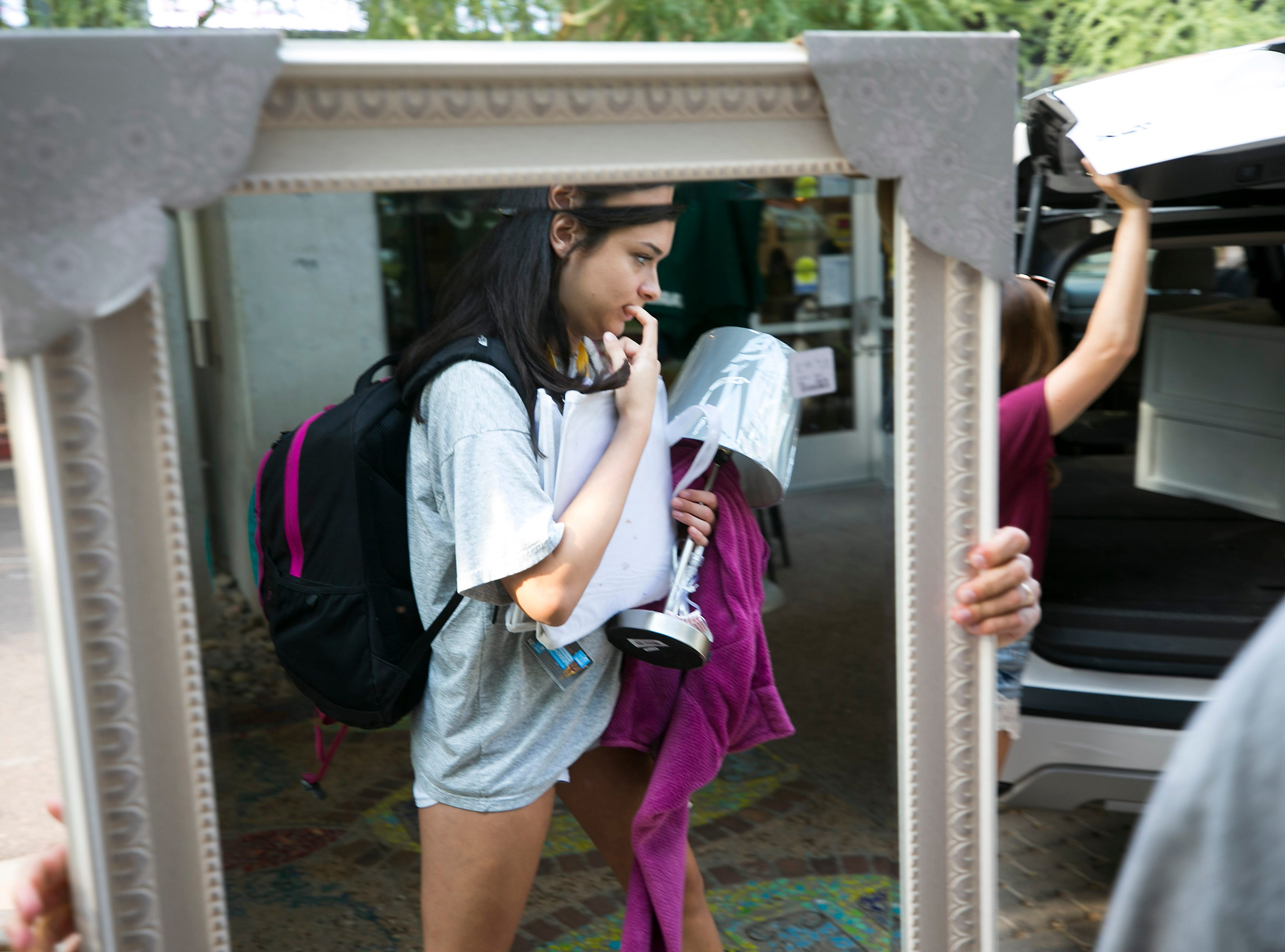 Incoming freshman Claire Stroud of Newbury Park, California, is seen reflected in her mirror while moving into her dorm at Taylor Place on the ASU downtown Phoenix campus on Aug. 10, 2018.