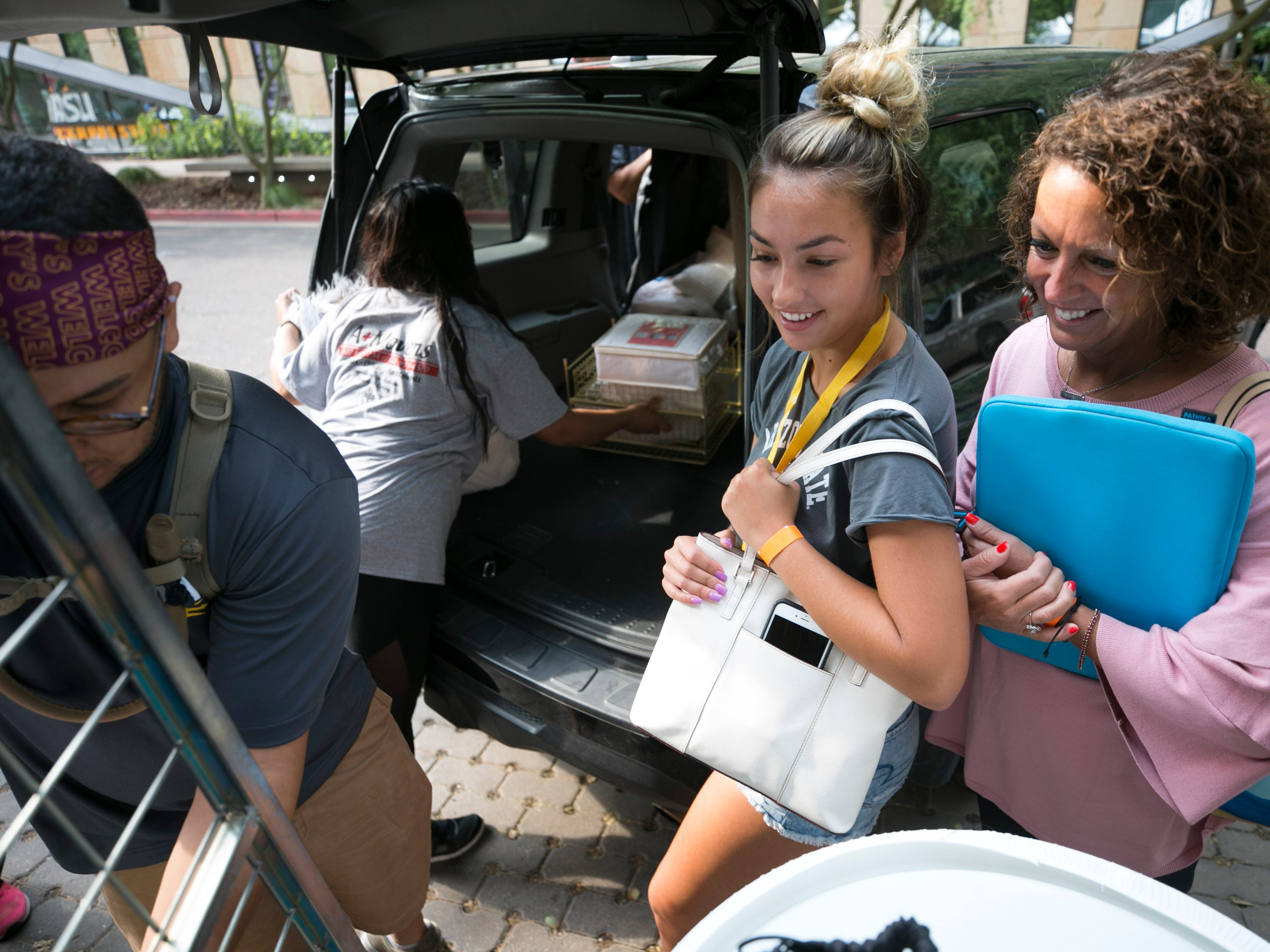 Incoming freshman Isabella Wilcox (center) of Dallas and her mother, Lisa Wilcox, watch as they receive help moving into Isabella's dorm at Taylor Place on the downtown Phoenix campus on Aug. 10, 2018.
