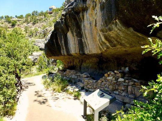 El sendero de la isla pavimentada, un circuito de 0.9 millas, zigzaguea 185 pies hacia Walnut Canyon para llegar a numerosos refugios de rocas apiladas con arcilla.