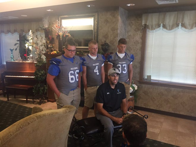 Joined by his Cedar Crest players, from left, Nate Sheaffer, Logan Horn and Brody Dunlop, Cedar Crest football coach Rob Wildasin gives an interview at Lancaster-Lebanon Football Media Day on Friday.