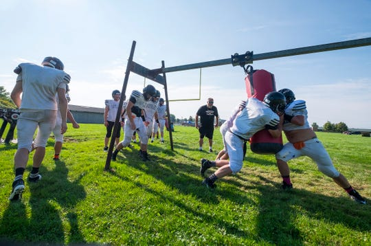 Marine City High School football players push a sliding bag during practice Friday, Aug. 10, 2018.