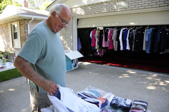 Jim Cook  looks through a pile of sweatshirts on the M-29 to M-25 Yard Sale Trail on Friday, Aug. 10, 2018.