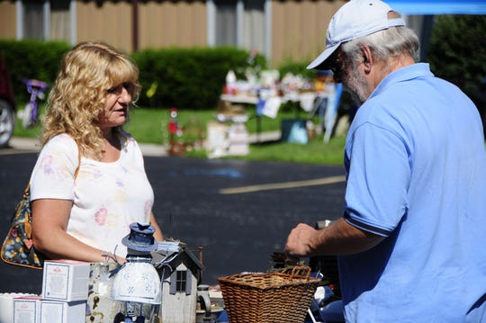 Darlene Wilson bargains with George Singer on the M-29 to M-25 Yard Sale Trail on Friday, Aug. 10, 2018.