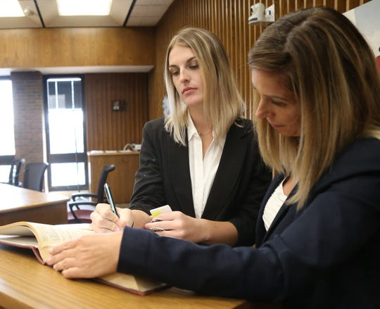 City of Poughkeepsie Police officer Amanda Rose signs the city oath book alongside chamberlain, Deanne Flynn, during the swearing in ceremony for six new officers at City Hall on August 10, 2018.