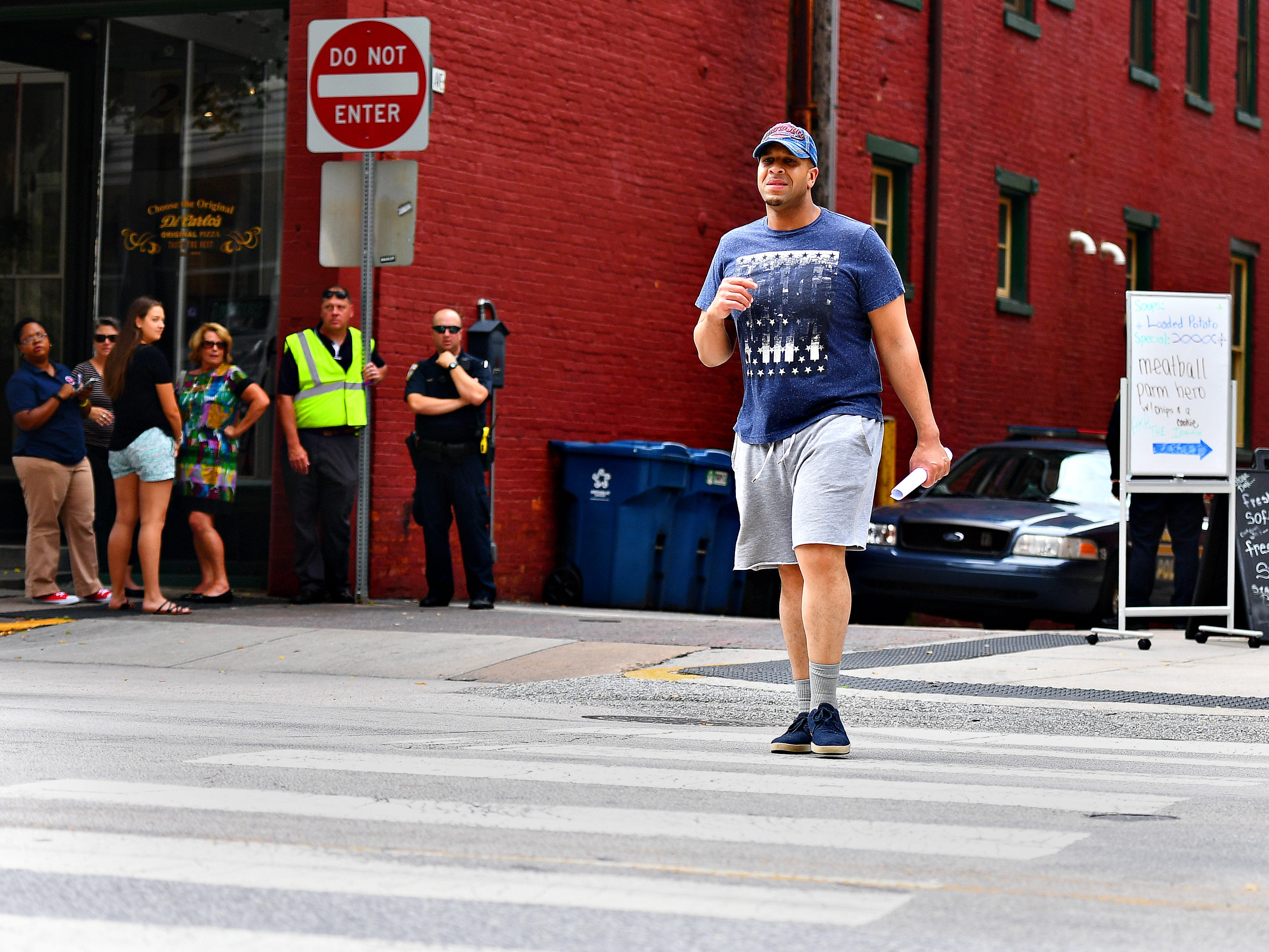 Police Officer Rich Kehler III, left, looks on as David Saulisbury crosses North George Street at Clarke Ave as York City Police conduct pedestrian safety enforcement detail in York City, Friday, Aug. 10, 2018. Dawn J. Sagert