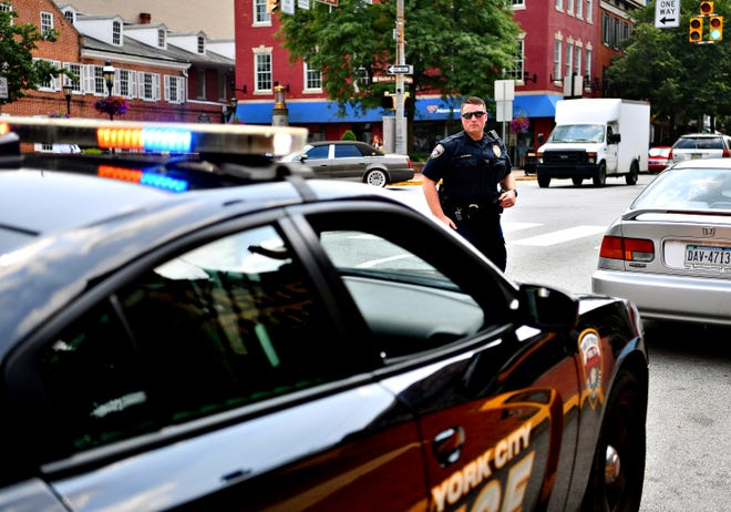 York City Police Officer Galen Detweiler returns to his squad car after stopping a driver who violated pedestrian safety during an enforcement detail at the intersection of North George Street and Clarke Avenue in York City, Friday, Aug. 10, 2018. Dawn J. Sagert