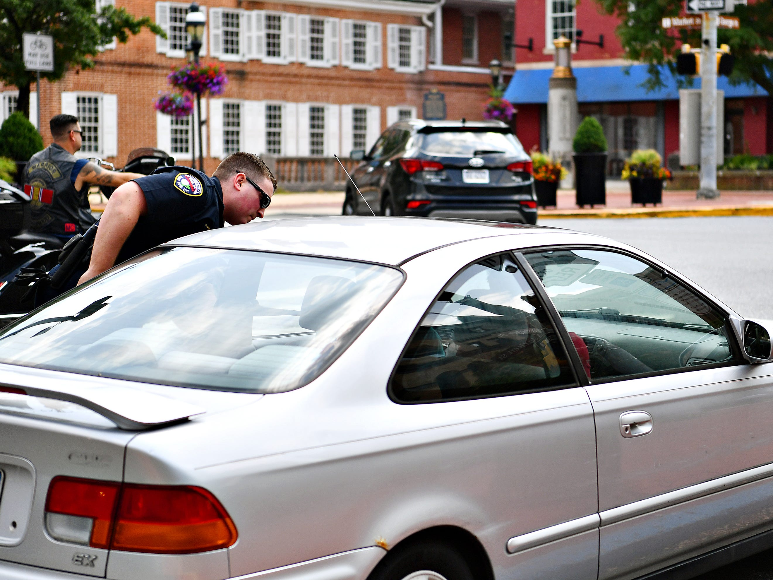 York City Police Officer Galen Detweiler stops a driver who violated pedestrian safety during an enforcement detail at the intersection of North George Street and Clarke Avenue in York City, Friday, Aug. 10, 2018. Dawn J. Sagert