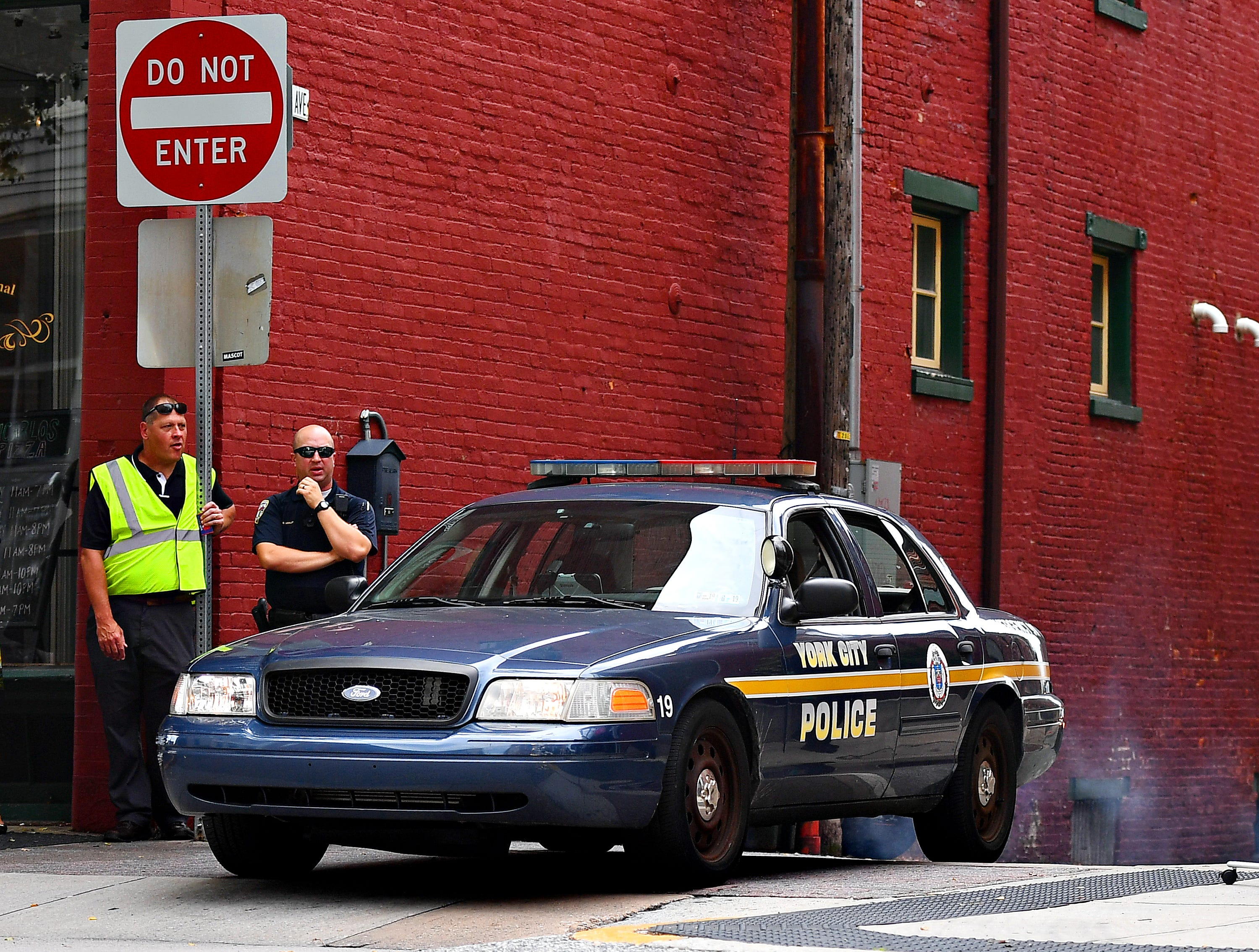 York City Police Officer Rich Kehler III, left, looks on after dispatching an officer to pursue a driver who violated pedestrian safety laws in a crosswalk at the intersection of North George Street and Clarke Avenue in York City, Friday, Aug. 10, 2018. Dawn J. Sagert