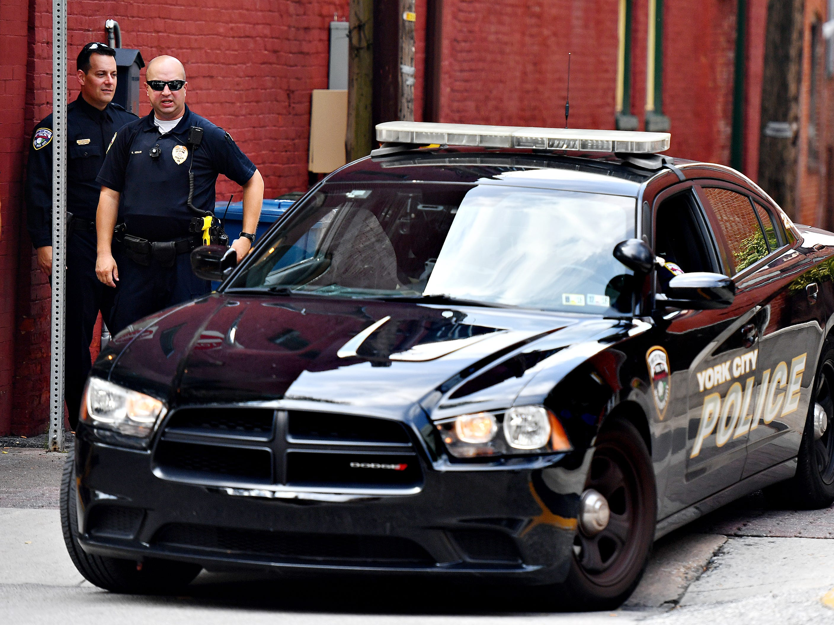 York City Police Officer's Derek Hartman, left, and Rich Kehler III, look on after dispatching an officer to pursue a driver who violated pedestrian safety laws in a crosswalk at the intersection of North George Street and Clarke Avenue in York City, Friday, Aug. 10, 2018. Dawn J. Sagert
