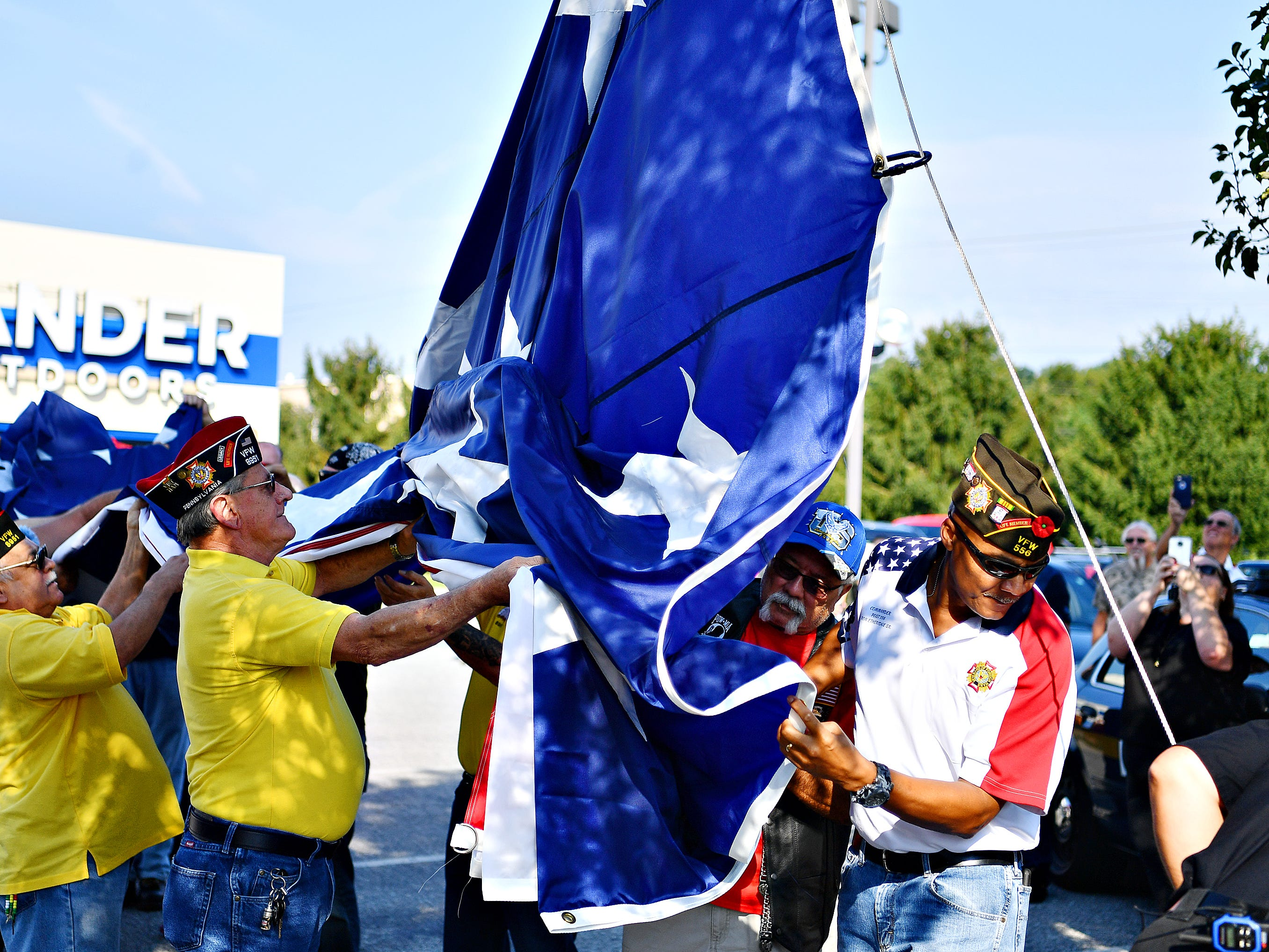 Volunteers hold an 80 by 40 foot flag as it is secured to the pole at Gander Outdoors in West Manchester Township, Friday, Aug. 10, 2018. Dawn J. Sagert