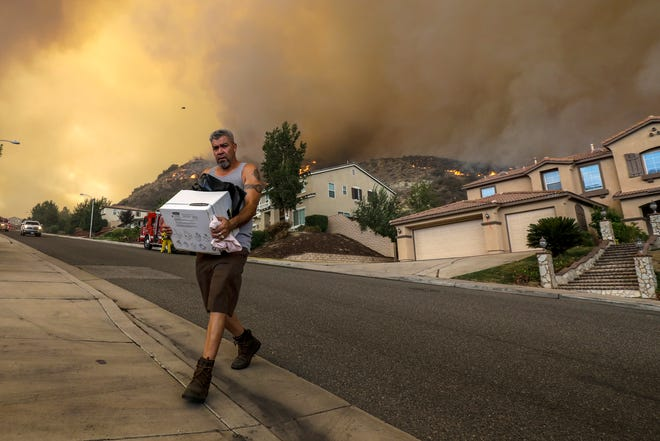 Manuel Trujillo packs his belongings as flames from the Holy fire threaten his home in Lake Elsinore, Calif., on Thursday, Aug. 9, 2018. (Irfan Khan/Los Angeles Times/TNS)