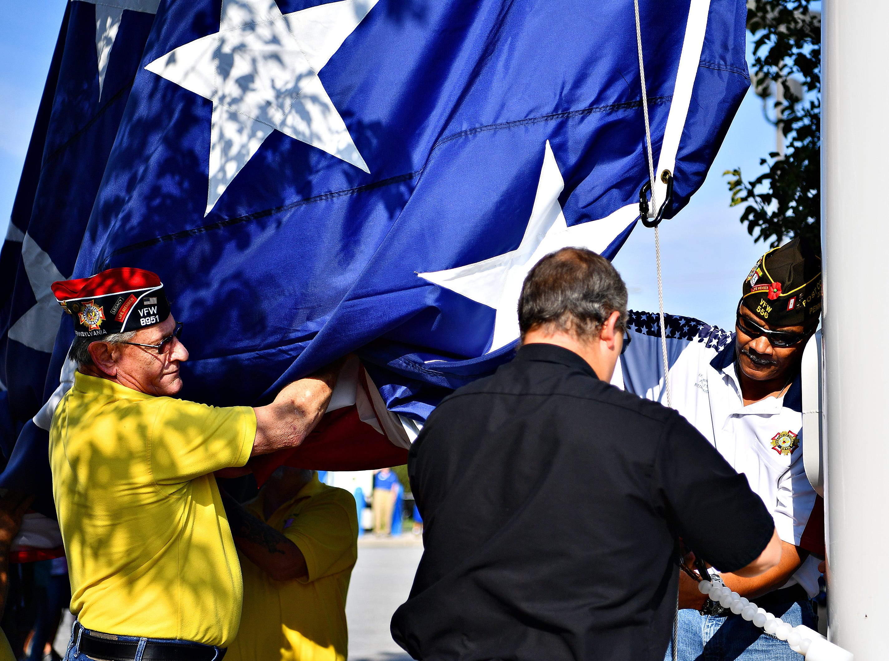From left, Bob Shank, of West York Borough VFW, Gander Outdoors Gearsmith Bill Maurer, and Ron Etheridge, of VFW 556, secure the flag to the pole as Gander Outdoors ceremoniously raises their 80 by 40 foot American flag at their store in West Manchester Township, Friday, Aug. 10, 2018. Dawn J. Sagert