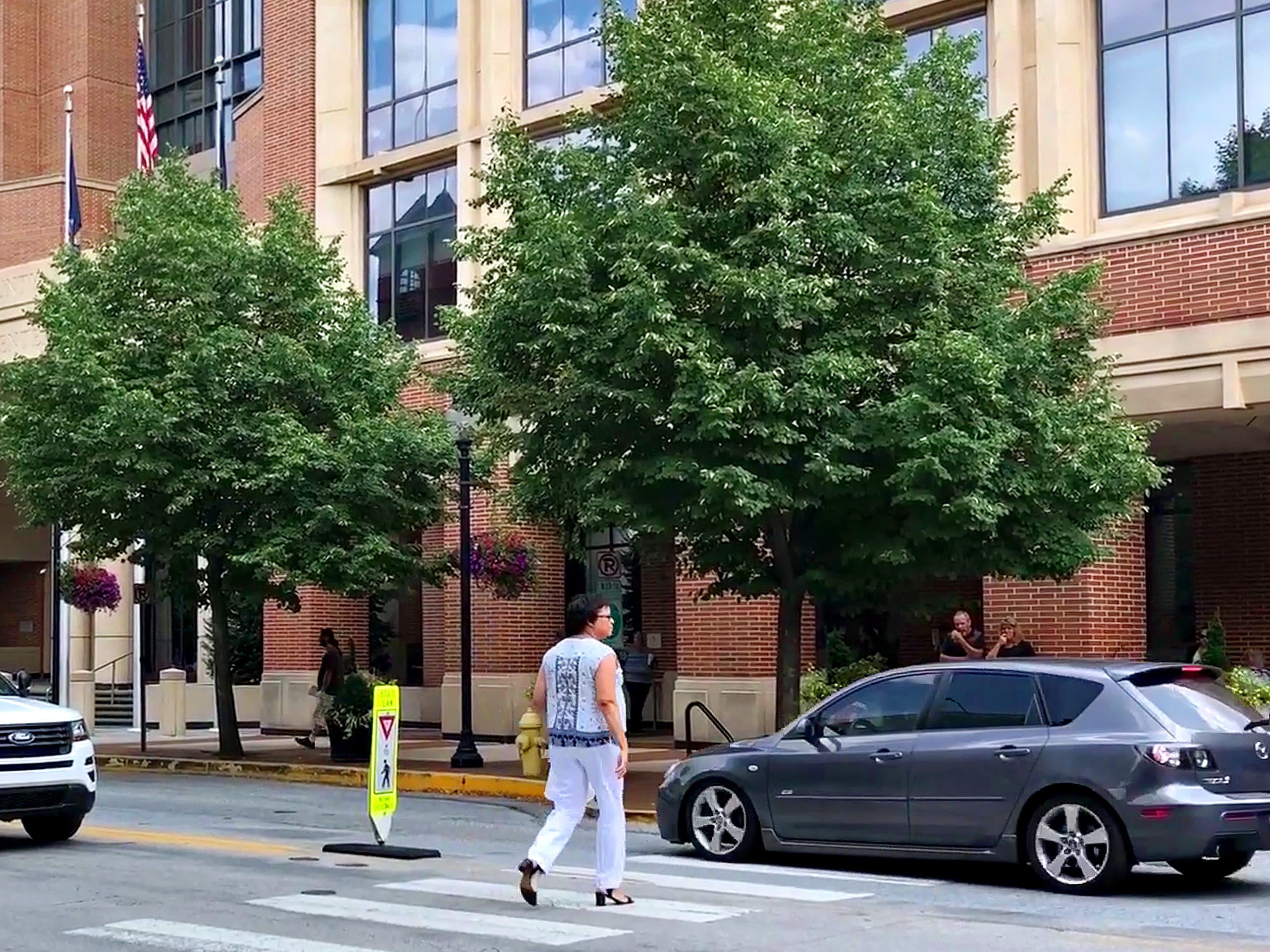 A driver crosses a crosswalk in front of a pedestrian as York City Police conduct pedestrian safety enforcement detail at the intersection of North George Street and Clarke Avenue over the lunch hour in York City, Friday, Aug. 10, 2018. Dawn J. Sagert