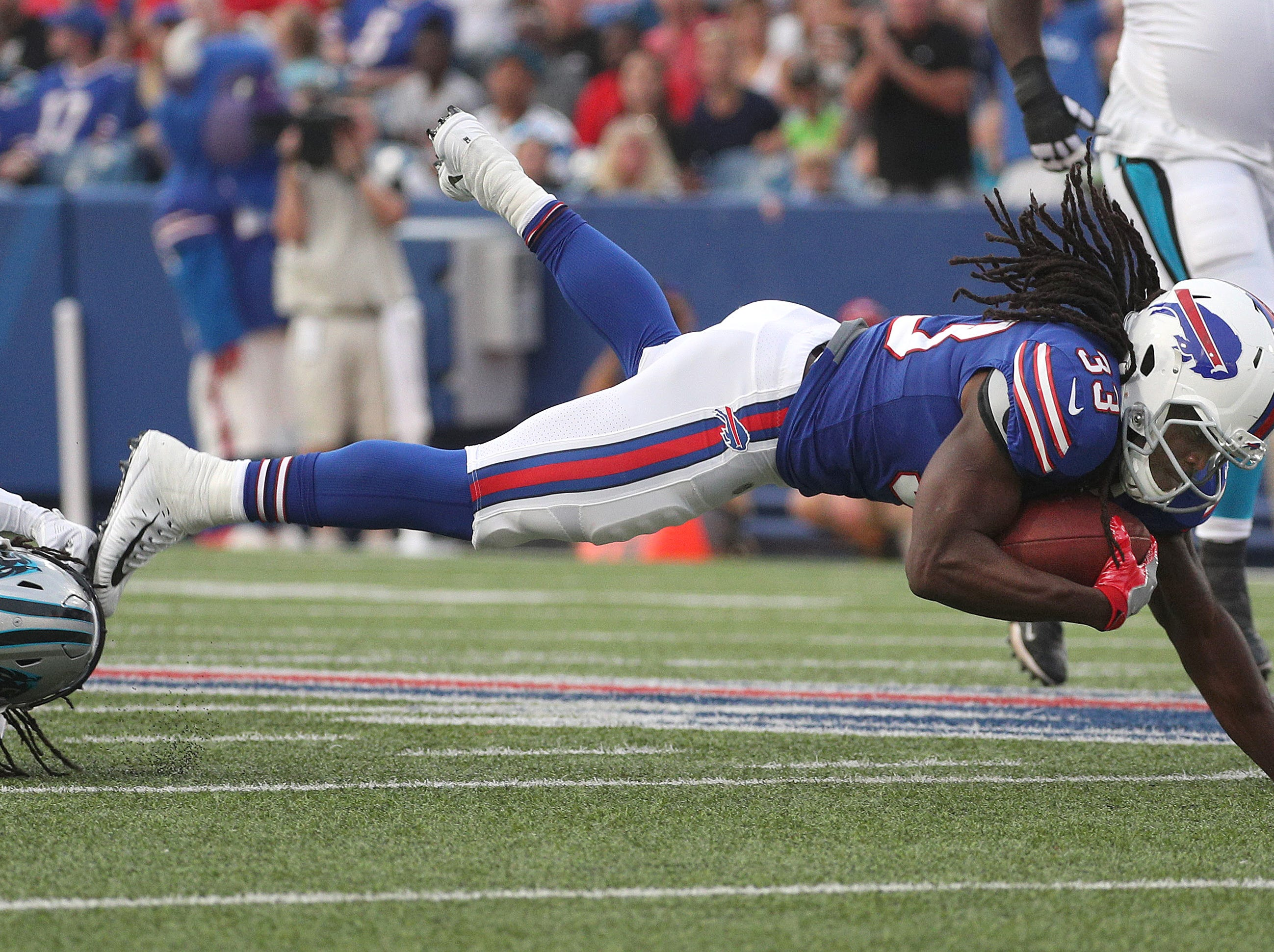 Bills running back Chris Ivory is tripped up by Carolina's Donte Jackson.