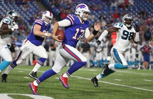 Bills quarterback Josh Allen tucks the ball and runs around the end.