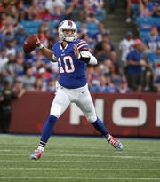 Bills quarterback AJ McCarron looks downfield and makes a throw.