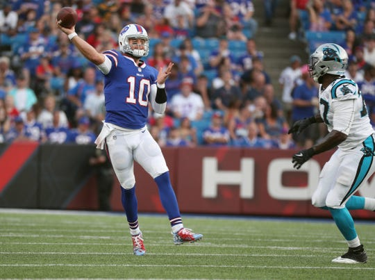 Bills quarterback AJ McCarron makes an off balance throw under pressure.