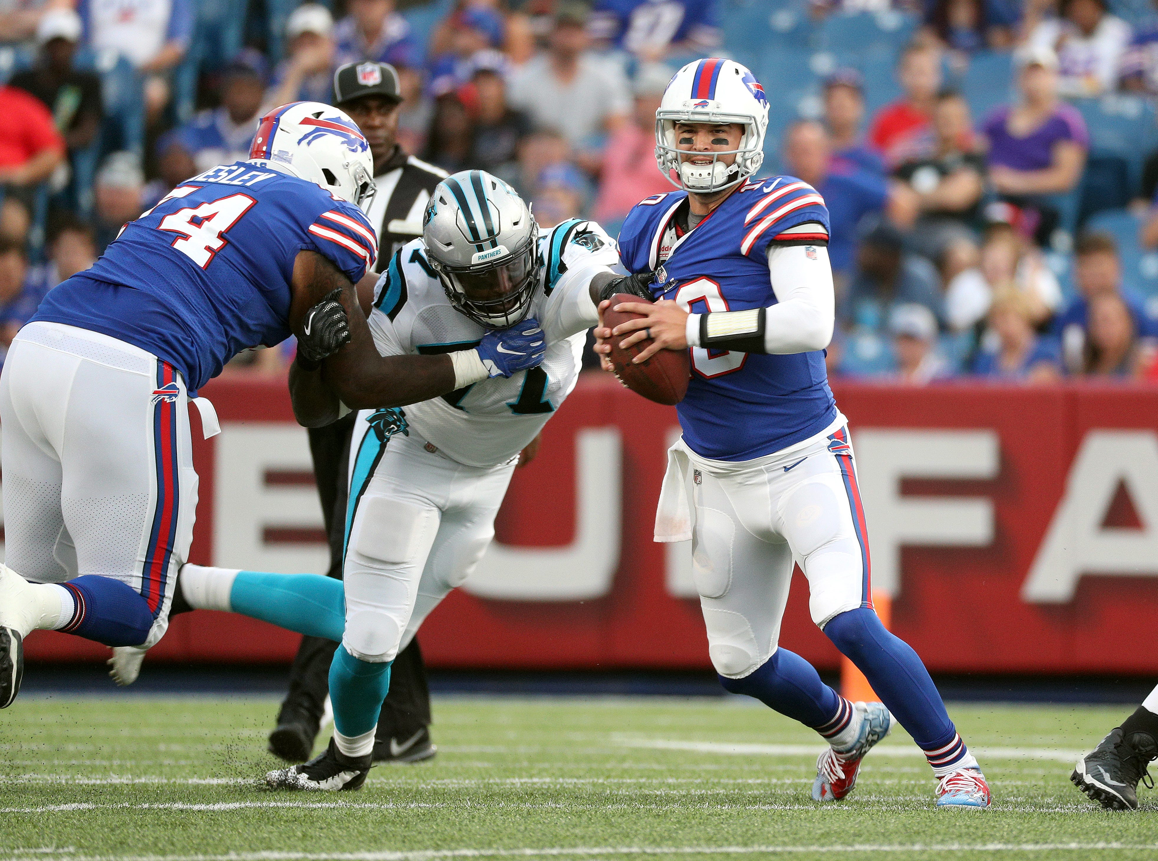 Bills quarterback AJ McCarron escapes the grasp of Carolina's Zach Moore.