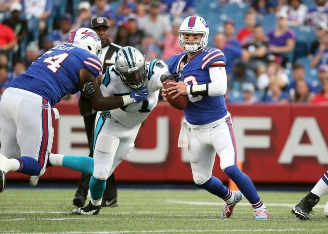Bills quarterback AJ McCarron escapes the grasp of Carolina's Zach Moore.