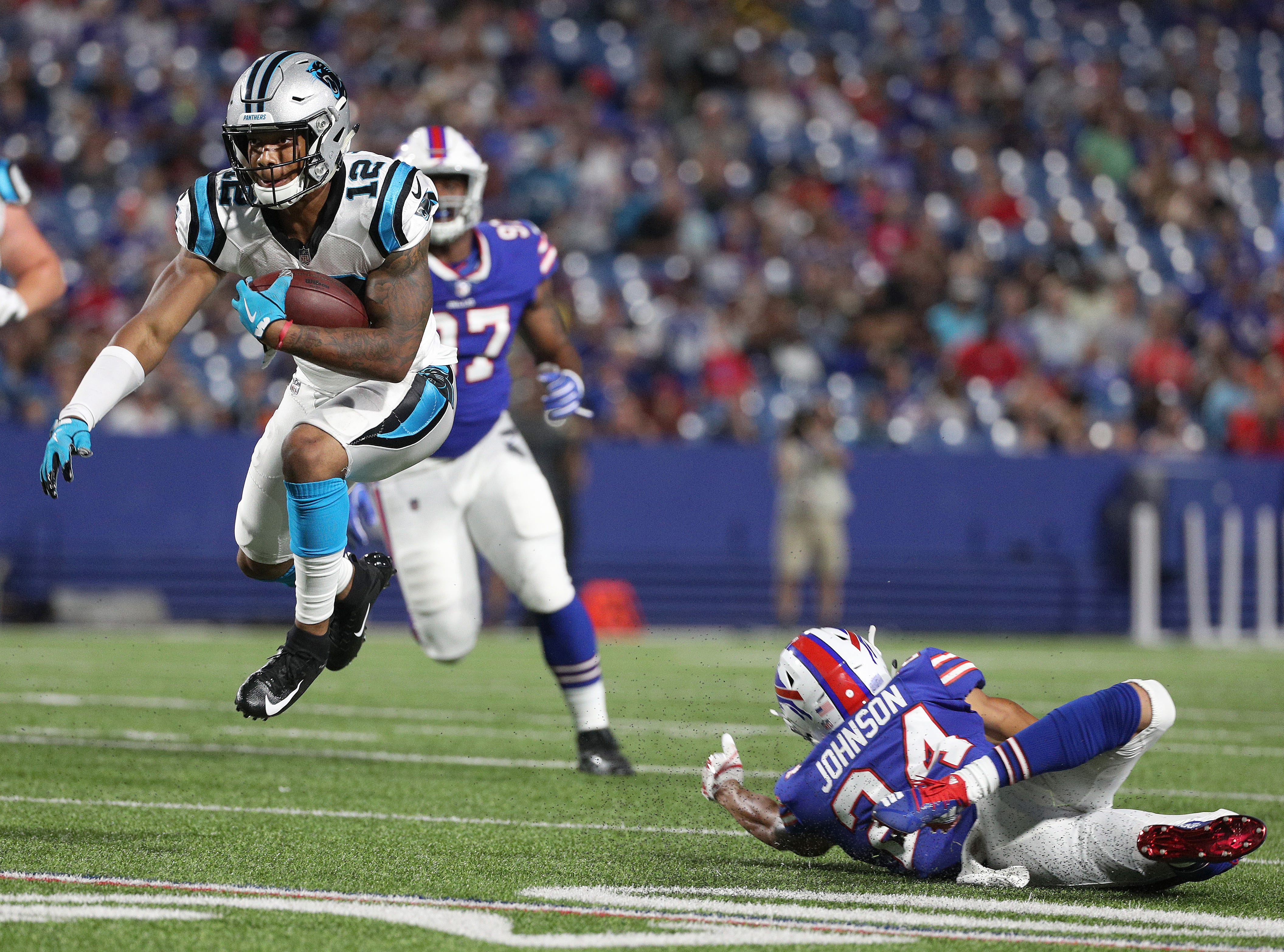 Carolina's DJ Moore (12 ) jumps over Bills Taron Johnson for extra yards.