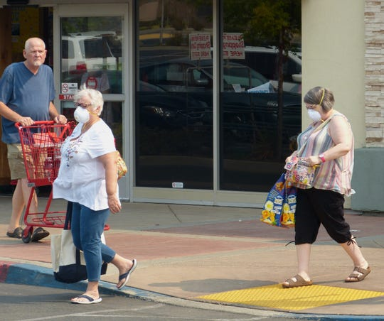 Sandi Duncan, foreground, and Amy Balk, both of Redding, donned masks due to the wildfire smoke during a Friday grocery outing.