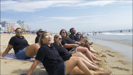 Members of the OCPD dispatch team sit on the beach during the lip sync video.