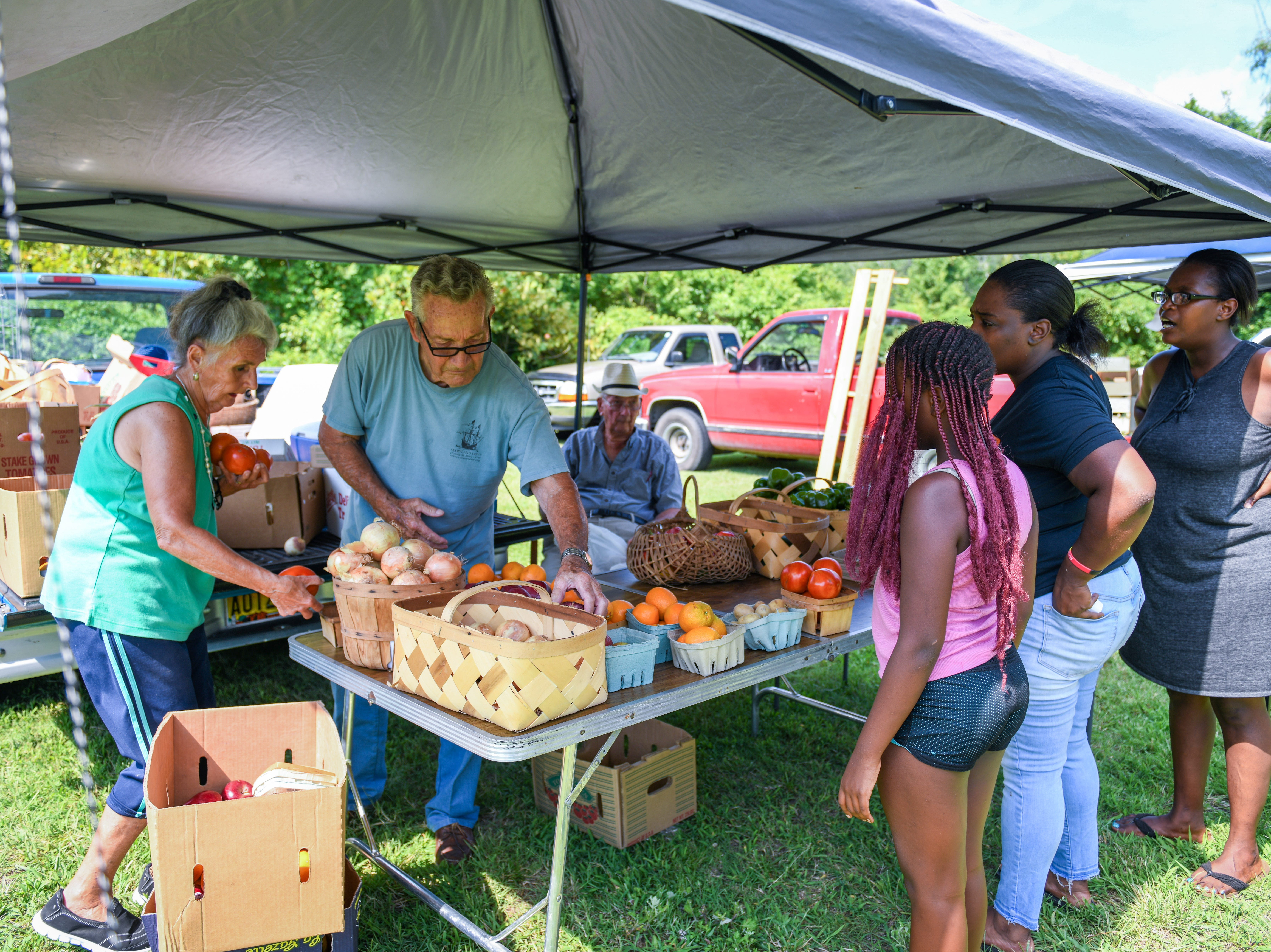 Katie Turner and David Mcinturff sell produce at the Princess Anne farmers market on August 9.