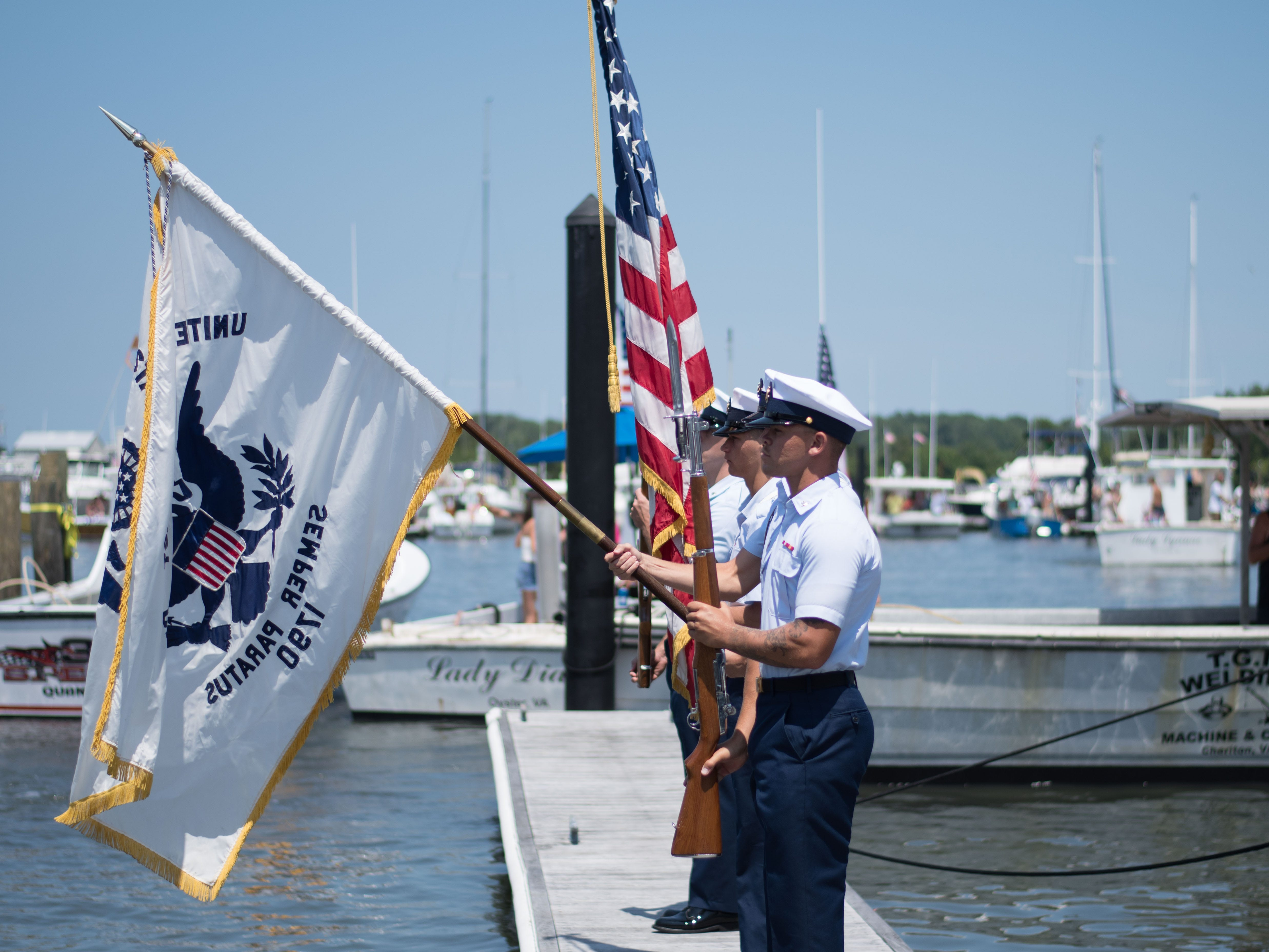 Member of the U.S. Coast Guard Auxiliary stand at attention during the Pledge of Allegiance on Sunday, Aug. 5.
