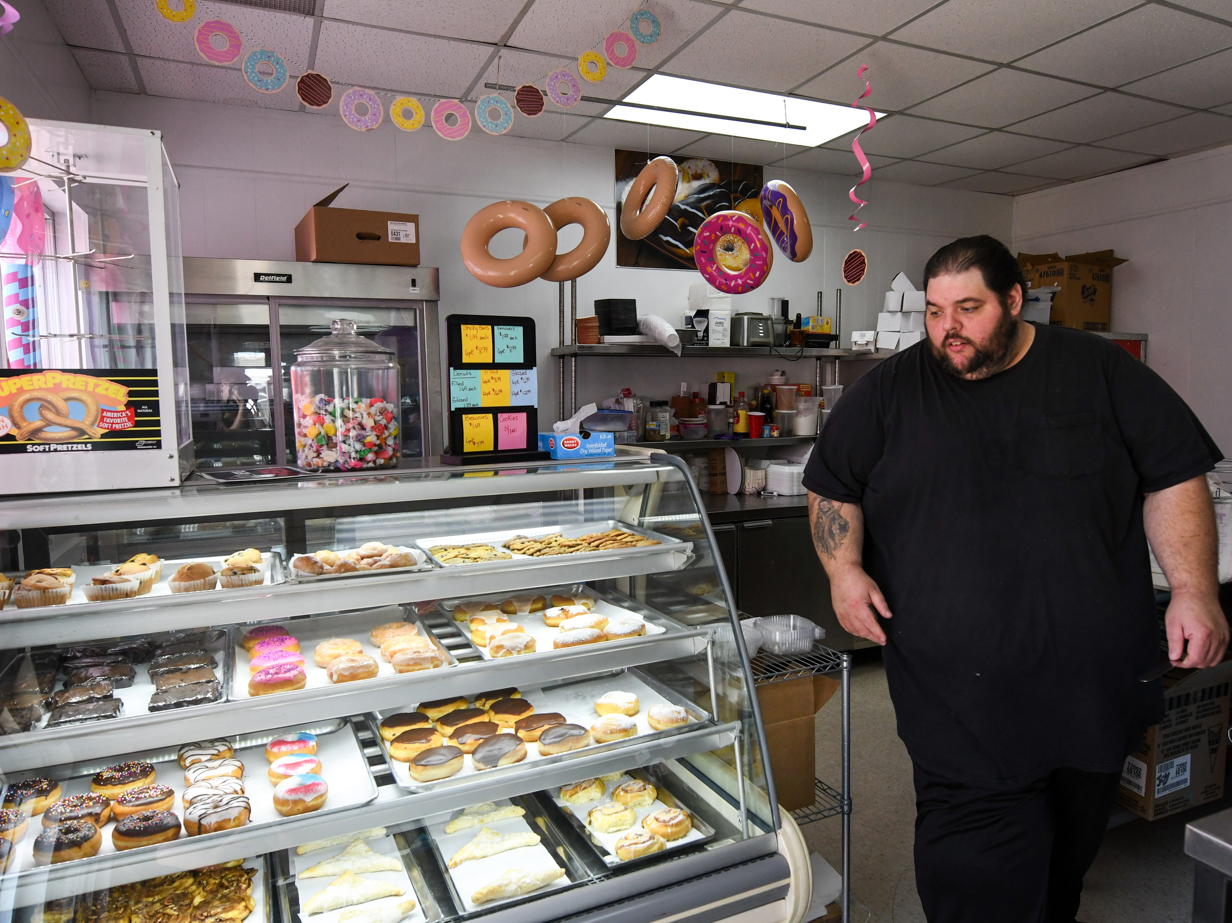 Owner John Konkel walks to the front of the doughnut display case at new bakery Johnnysweets in Crisfield on August 9.