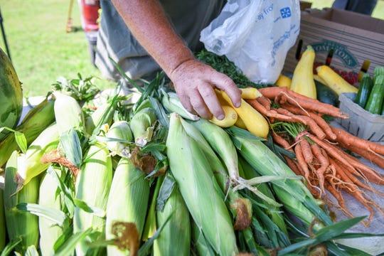 Farmers organize produce at the Princess Anne farmers market on Thursday, Aug 9, 2018.