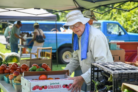 Sidney Merrill sets up a produce table at the Princess Anne farmers market on August 9.
