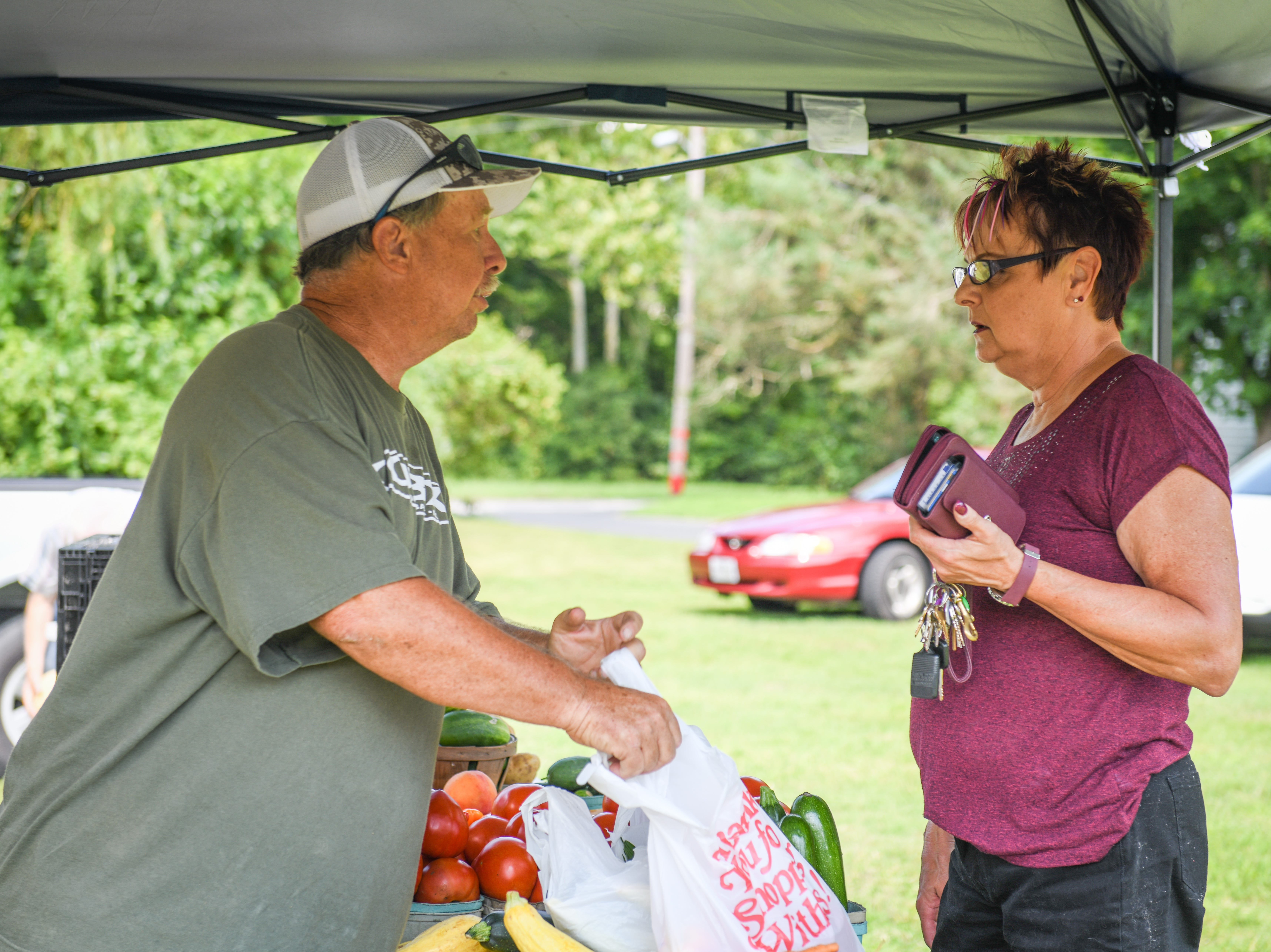 Ken Robinson sells produce to a customer at the Princess Anne farmers market on August 9.