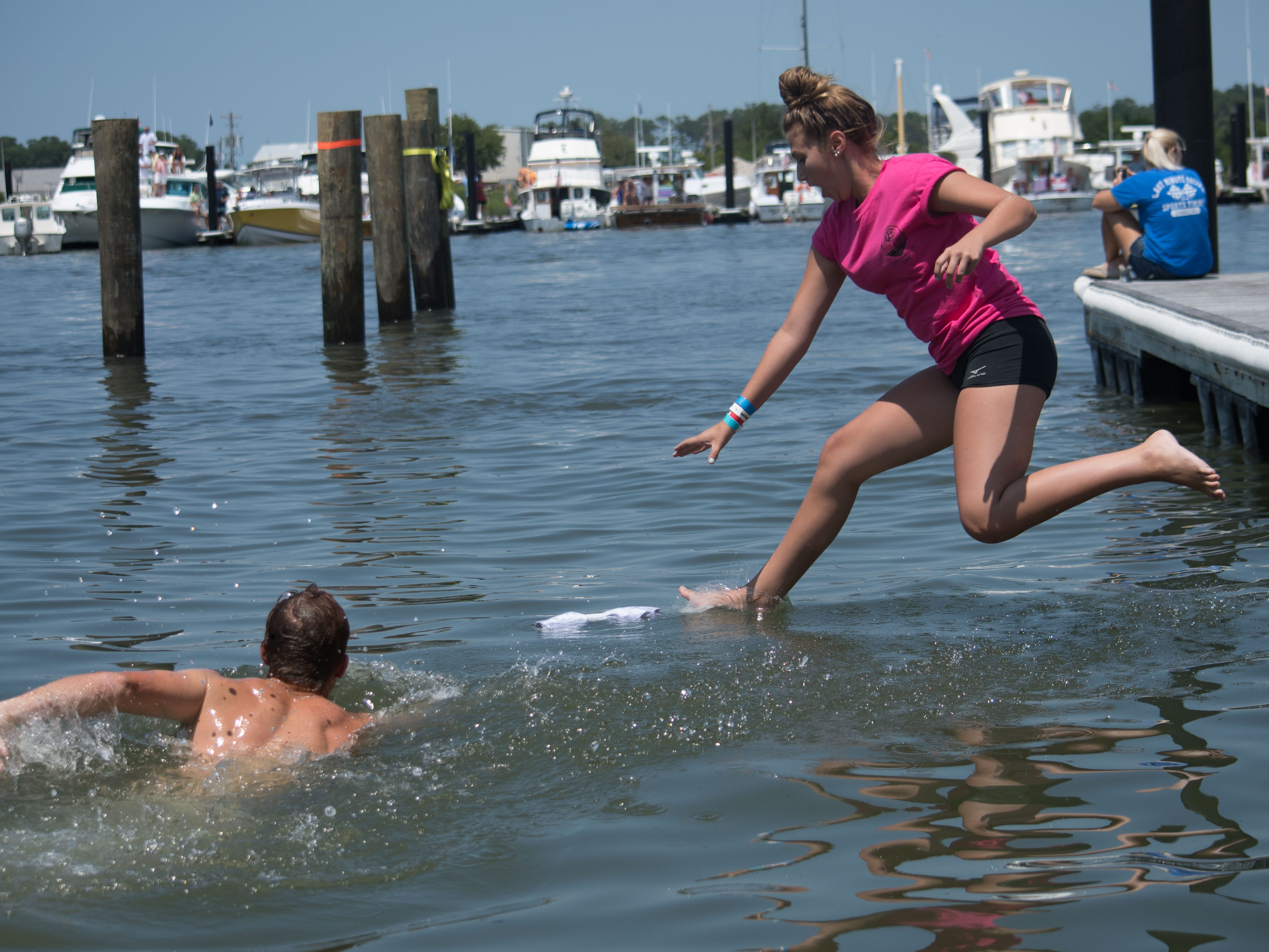 Two members of the crowd leap into the bay in an attempt to obtain a T-shirt throw by a passing participating boat.
