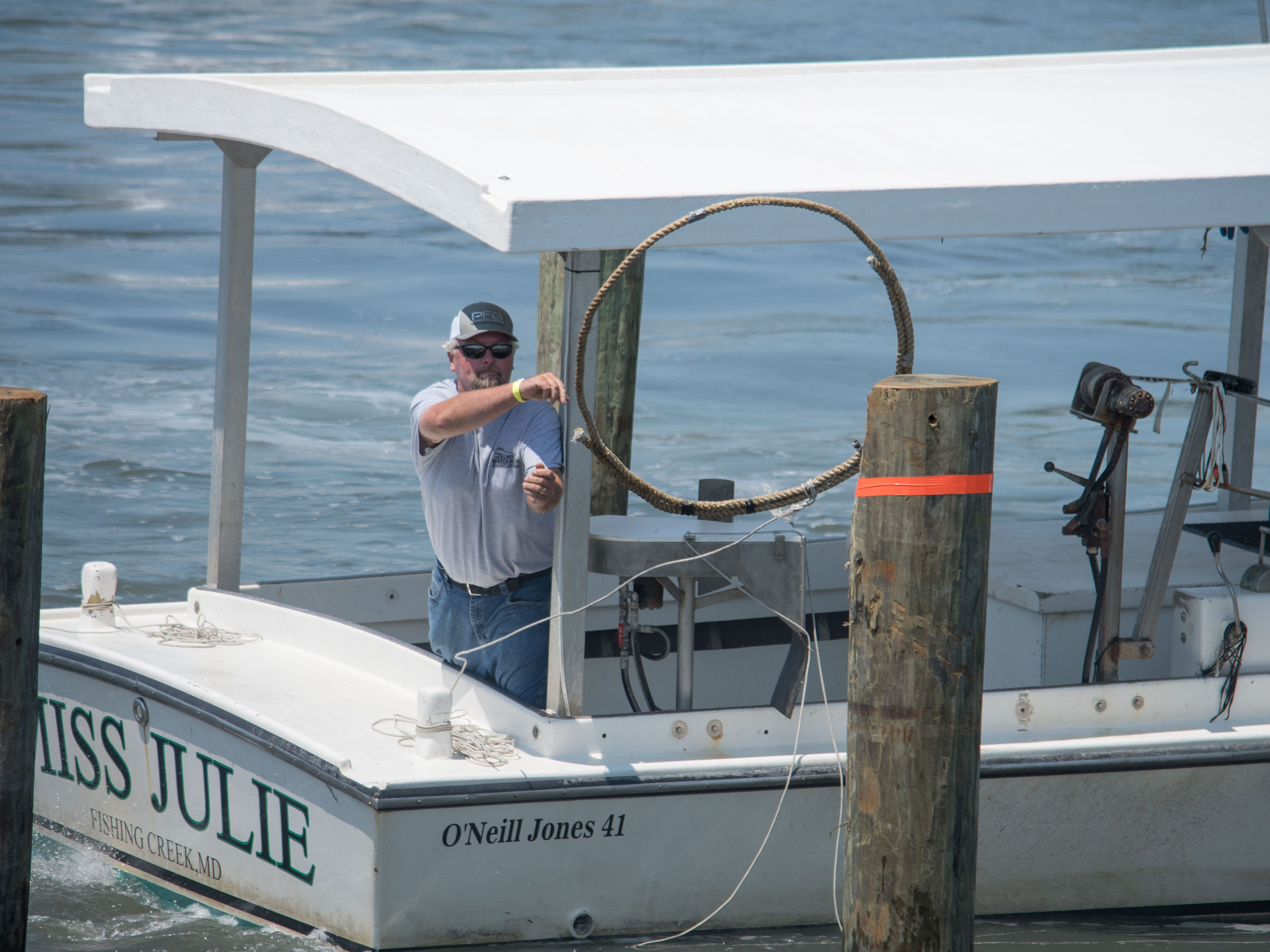 John Ashton, captain of Miss Julie, hurls a piling hoop during the Boat Docking Contest on Sunday, Aug 5, in Cape Charles.