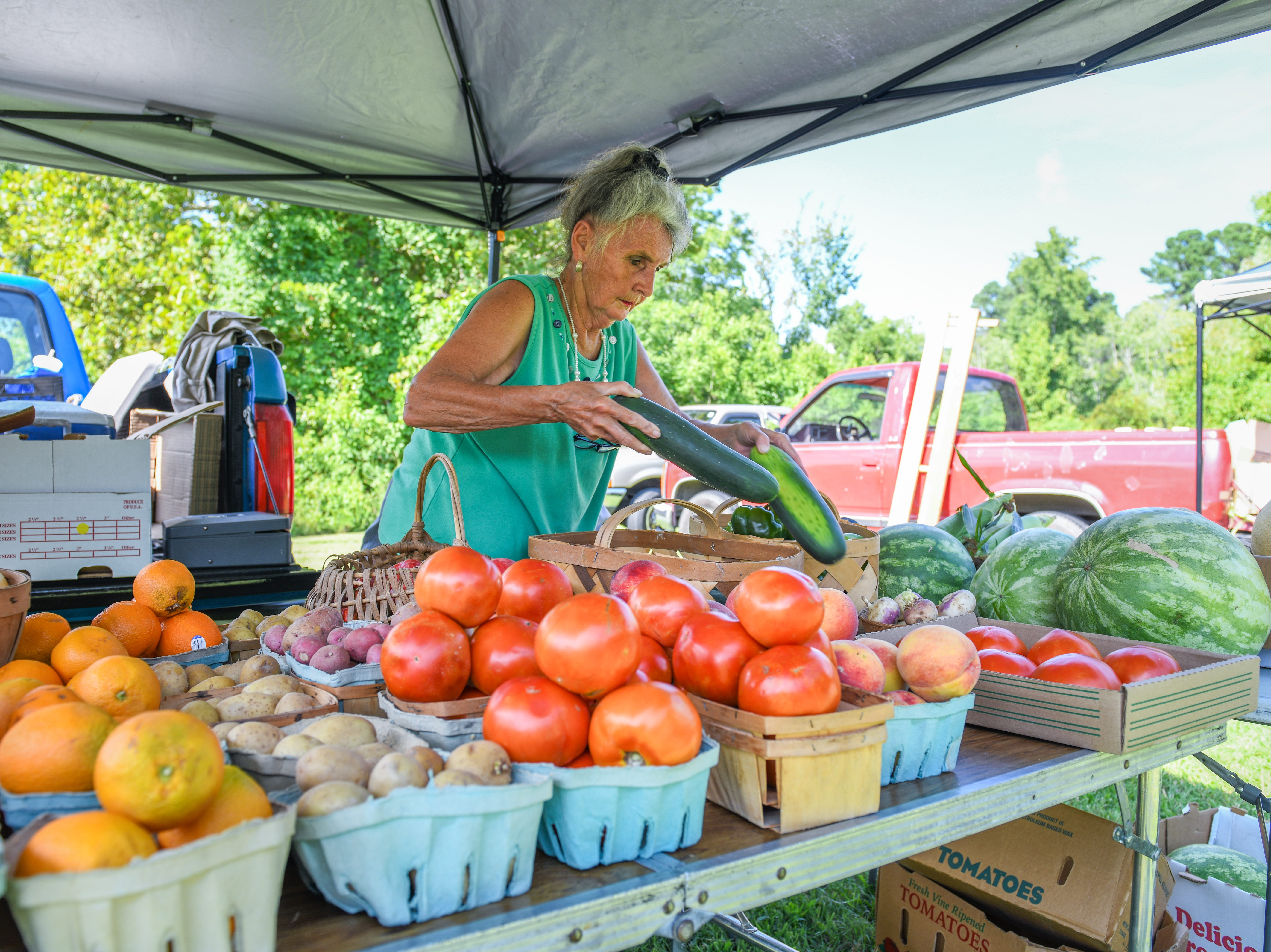 Katie Turner arranges produce at the Princess Anne farmers market on August 9. She piled her table with tomatoes, onions, potatoes, peppers and watermelon before leaving for work at Rite Aid.