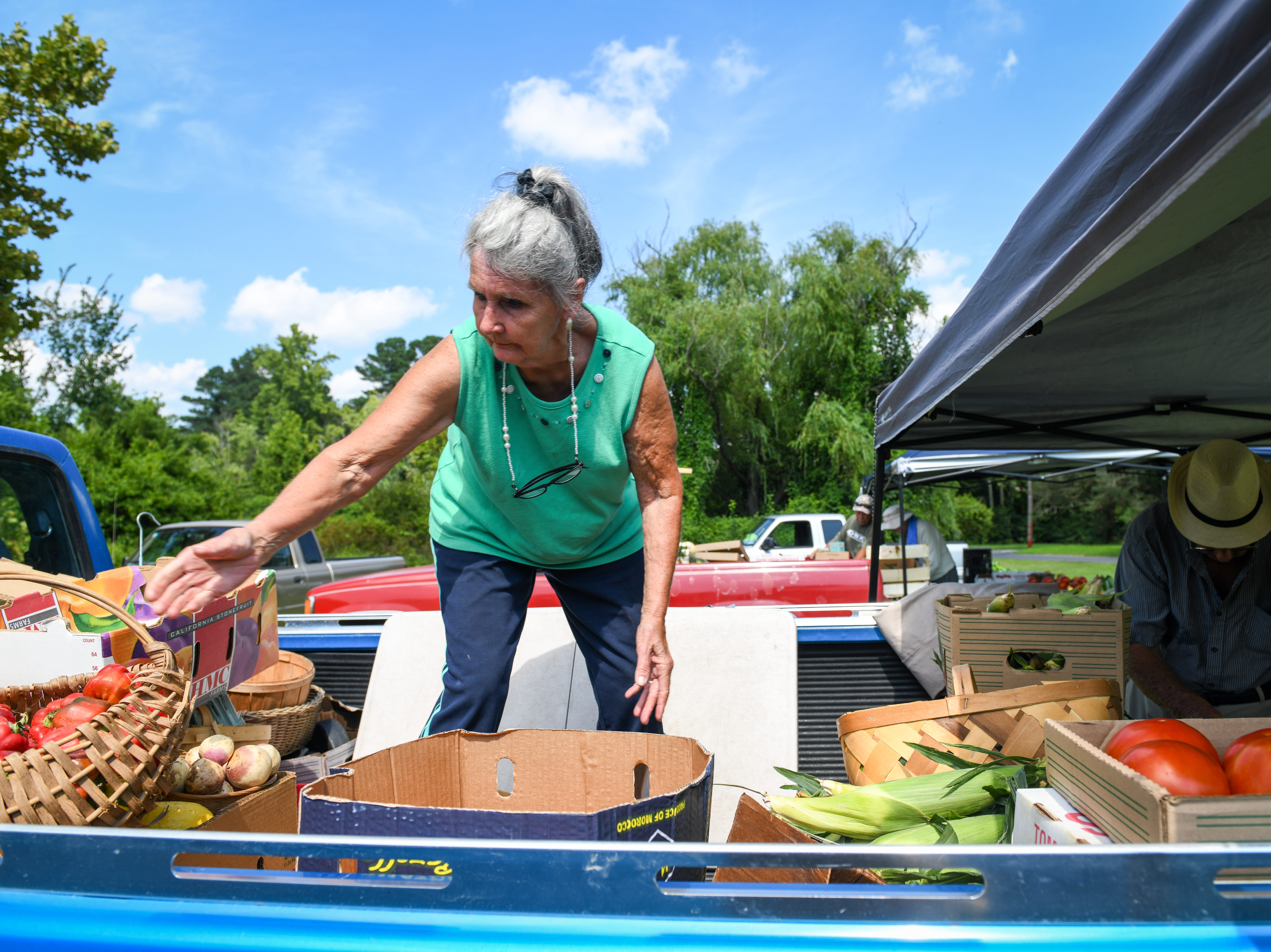 Katie Turner pulls produce out of at truck to sell at the Princess Anne farmers market on August 9.