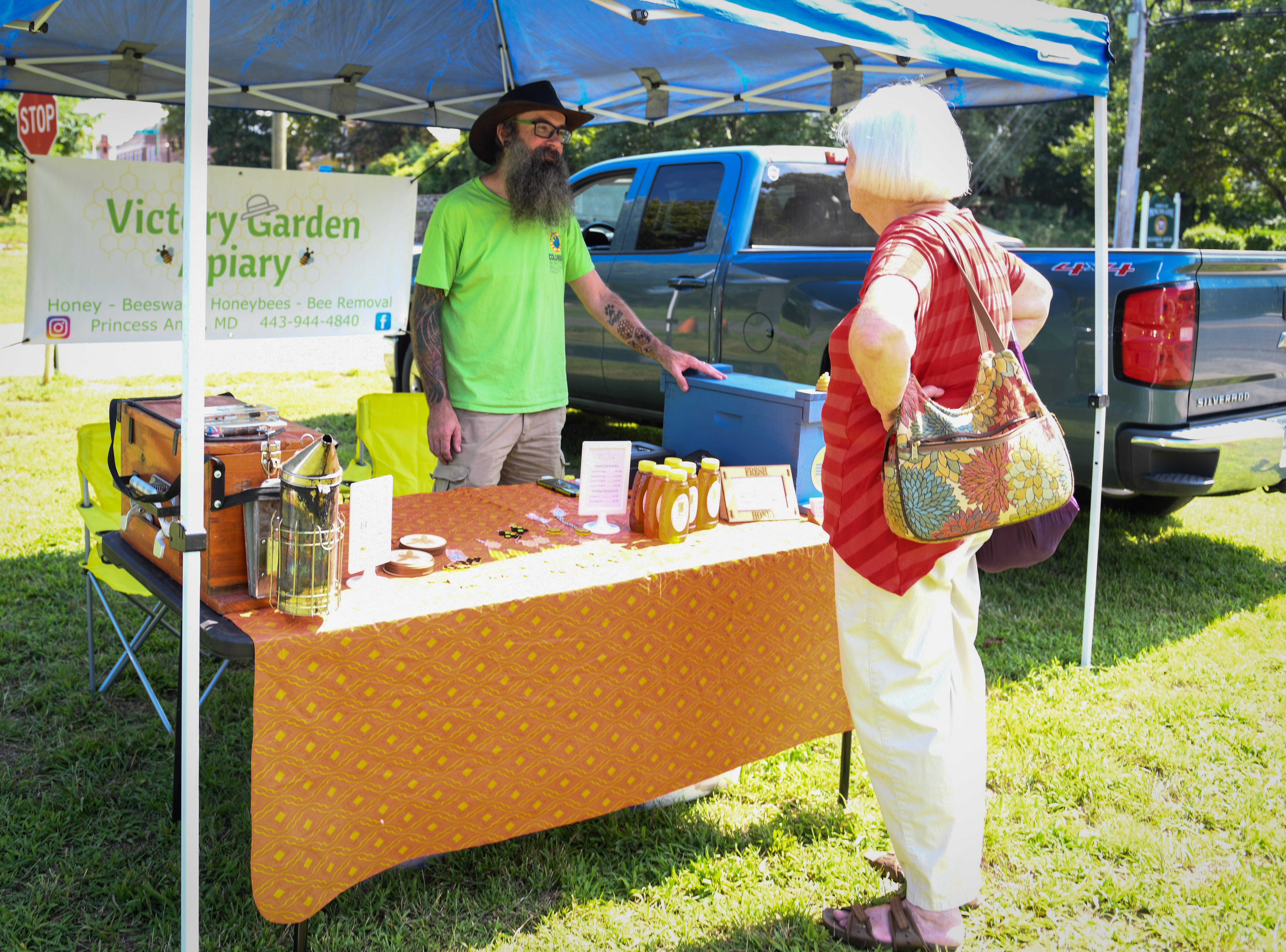 Jim Leether of Victory Garden Apiary talks with a customer at the Princess Anne farmers market on August 9.