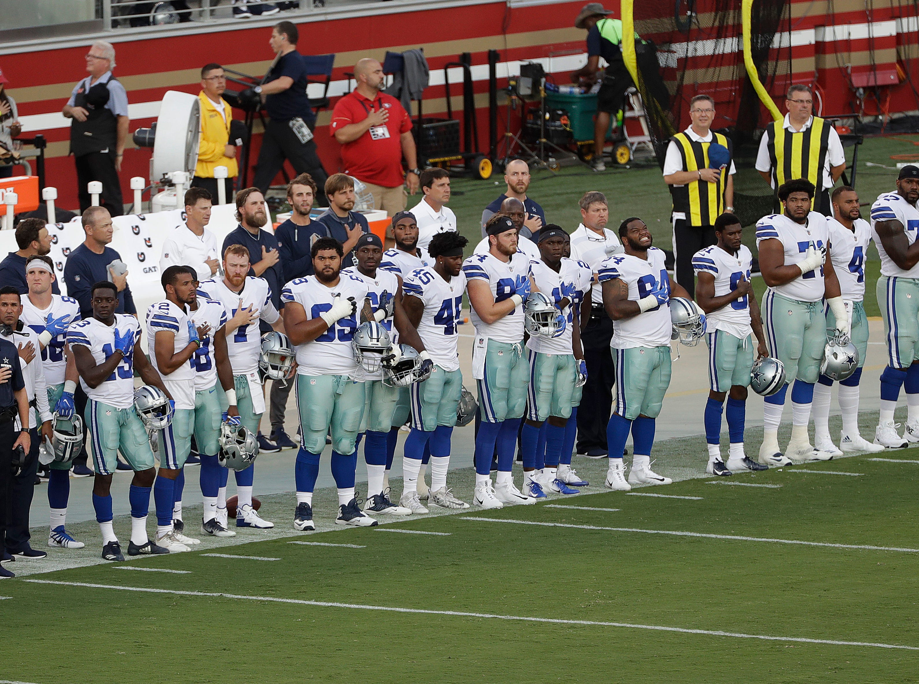 Dallas Cowboys players stand during the national anthem before an NFL preseason football game against the San Francisco 49ers in Santa Clara, Calif., Thursday, Aug. 9, 2018. (AP Photo/Jeff Chiu)