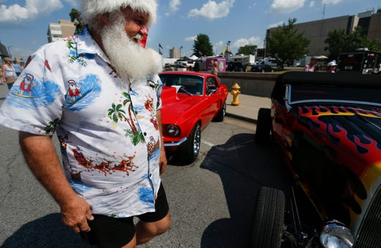 Wearing a Santa hat, Kerry Walton from Melbourne, Australia checks out classic cars during the Birthplace of Route 66 Festival on Friday, Aug. 10, 2018. Walton, who moonlights as a singing Santa Claus, is attending the festival for his second year in a row.