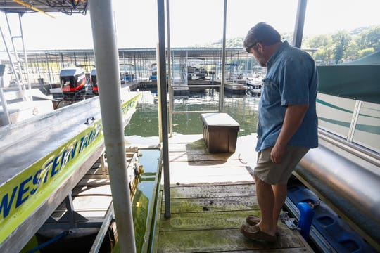 Scotty's Trout Dock, owner Lamar Patton, looks at otter feces on his dock on Friday, Aug. 10, 2018. Patton said otters have caused hundreds of dollars of damage to his boats and boats of customers.