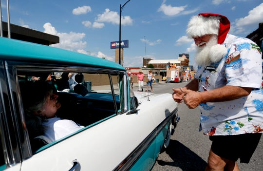 Wearing a Santa hat, Kerry Walton from Melbourne, Australia, gives two thumbs up to a passenger in a classic car driving on East St. Louis Street during the Birthplace of Route 66 Festival on Friday, Aug. 10, 2018. Walton, who moonlights as a singing Santa Claus, is attending the festival for the second year.
