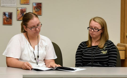 Advocates Jessica Matvick and Brianna Kalahar look at materials on cyber stalking during an interview Thursday, Aug. 9, at Anna Marie's Alliance in St. Cloud.